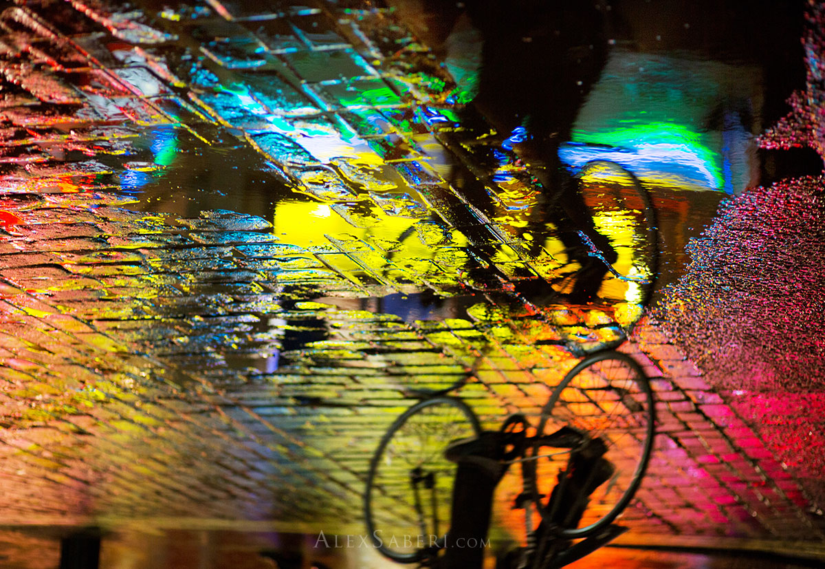 A cyclist cycles through a colourful puddle at night in London's Soho.